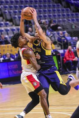 Mike Moore | The Journal Gazette Mad Ants guard Stephan Hicks collides with Skyhawks guard Brandon Goodwin while driving to the basket in the first period against College Park at Memorial Coliseum on Monday.