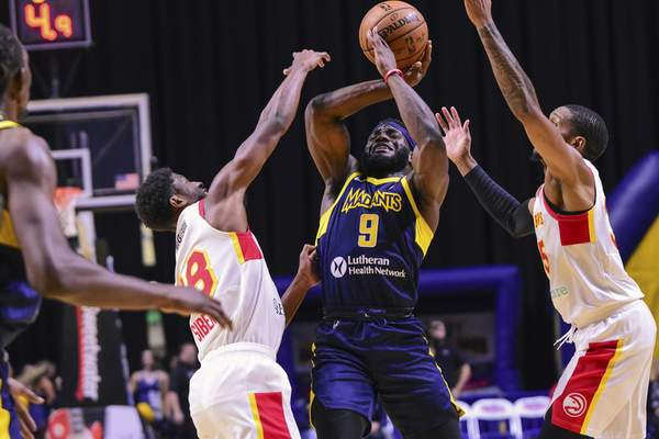 Mike Moore | The Journal Gazette Mad Ants guard Ike Nwamu gets tied up by College Park defenders in the first period at Memorial Coliseum on Monday.