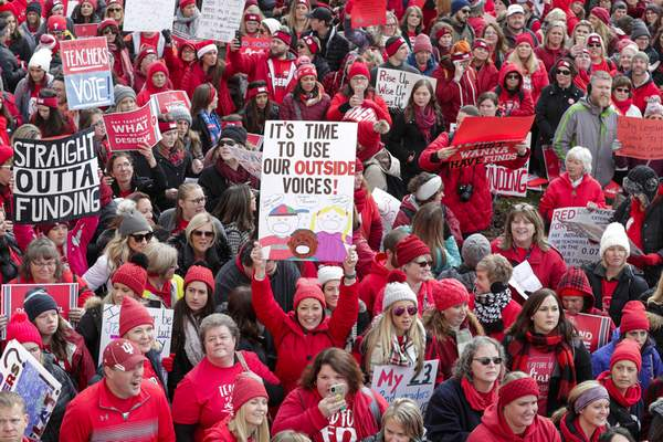 Thousands of Indiana teachers wearing red surround the Statehouse in Indianapolis on Tuesday for a rally calling for further increasing teacher pay in the biggest such protest in the state. (Associated Press photos)