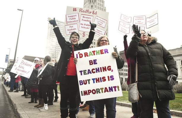 Michelle Davies | The Journal Gazette Educators from Adams Elementary School, from left, Anne Gaunt,  Valerie Brown and Suzi Tipton wave at passing motoristsduring a Red for Edrally Tuesday infront of the Allen County Courthouse.