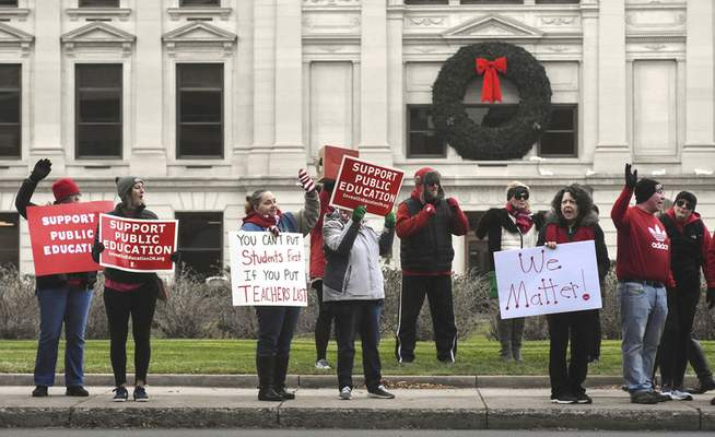 Michelle Davies | The Journal Gazette  Participantshold signs in support of public education during a Red for Ed rally in front of the Allen County Courthouse on Tuesday.