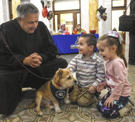 Superior Court Judge Charles Pratt visits with Hunter and Natalie Bennett as they pet Snyder, a therapy dog from Three Rivers Visiting Dogs, during Wednesday's Adoption Day.