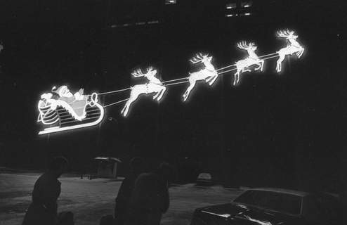 Pedestrians walk past the downtown Santa display in a photo dated Dec. 10 or 11, 1980. The holiday season of 1980 was the first time the display had been hung and lit together since 1958. (Journal Gazette file photo)