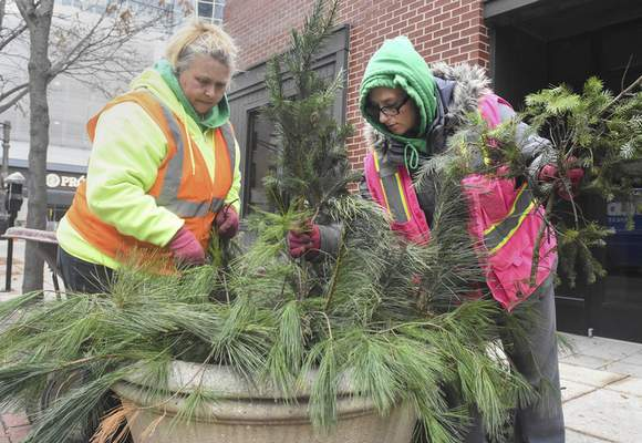 Michelle Davies | The Journal Gazette  Angela Lewis, left, and Donna Dennis,  both with Triscape Inc., work together on some holiday display planters downtown Thursday.