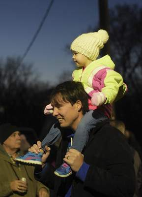 Sophia Guidinger, 2, sits on her father's shoulders in anticipation for the tree lighting during Christmas on Broadway.