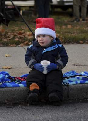 Christopher Southerland, 2, sits and enjoys a cup of hot chocolate Friday while waiting for the tree lighting during Christmas on Broadway.