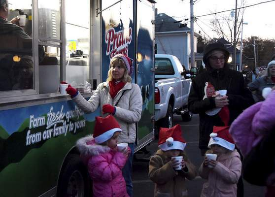 Terri Lothamer, inside the Prairie Farms truck, hands out hot chocolate and eggnog Friday during Christmas on Broadway.