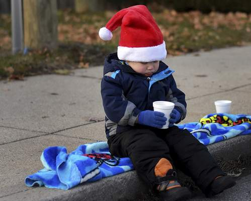 Christopher Southerland, 2, sits with his cup of hot chocolate while waiting for the tree lighting during Christmas on Broadway on  Friday.