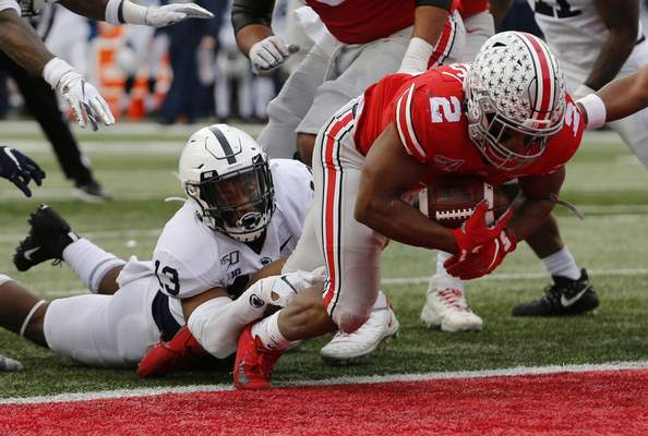 Ohio State running back J.K. Dobbins, right, drags Penn State linebacker Ellis Brooks into the end zone for a score during the first half of an NCAA college football game Saturday, Nov. 23, 2019, in Columbus, Ohio. (AP Photo/Jay LaPrete)