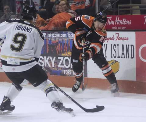 Katie Fyfe | The Journal Gazette  Komets' Kyle Haas goes to pass the puck while Wheeling Nailers' Yushiroh Hirano defends him during the first period at Memorial Coliseum on Saturday.