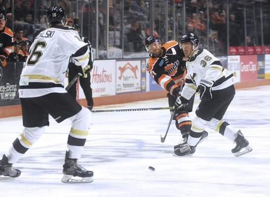 Katie Fyfe | The Journal Gazette  Komets' Shawn Szydlowski passes the puck during the second period against Wheeling Nailers at Memorial Coliseum on Saturday.