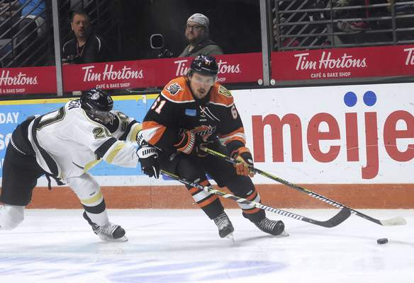 Katie Fyfe | The Journal Gazette  Komets' Taylor Ross chases after the puck while Wheeling Nailers' Steve Johnson defends him during the second period at Memorial Coliseum on Saturday.