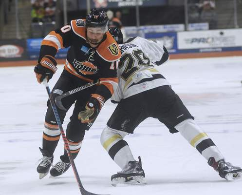 Katie Fyfe | The Journal Gazette  Komets' Brady Shaw chases after the puck while Wheeling Nailers' Steve Johnson defends him during the first period at Memorial Coliseum on Saturday.