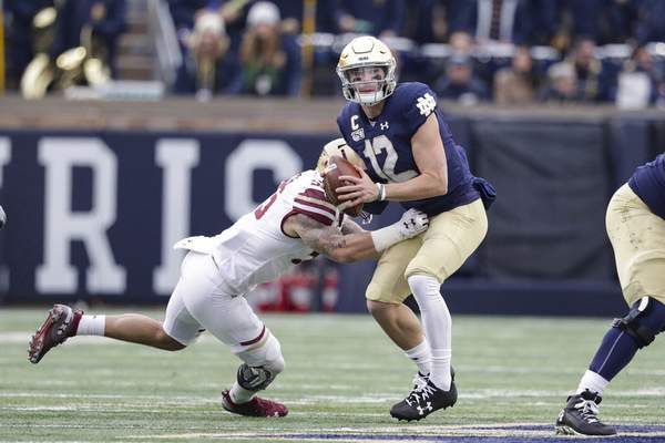 Notre Dame quarterback Ian Book is hit by linebacker Isaiah McDuffie in the first half Saturday in South Bend.