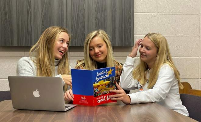 Courtesy photo  Lauryne Pearson, Arianna Betterly, and Dylinn Hertel check out the Spirit of America's guide book to New York City and Macy's Thanksgiving Day Parade, trying to decide which attraction they will visit first after marching in the parade.