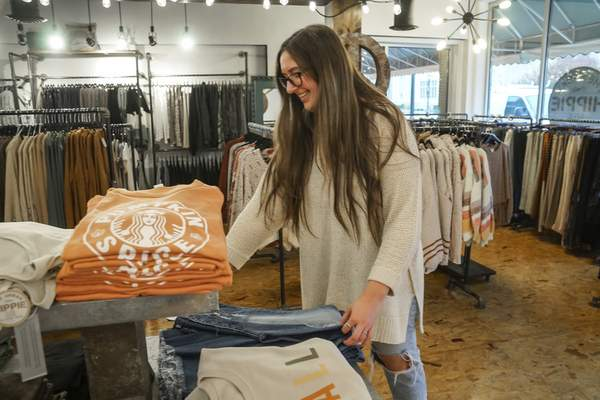 Mike Moore | The Journal Gazette Store manager Lauren Hire folds clothes at The Urban Hippie at 534 W. Berry St. on Tuesday 11.19.19