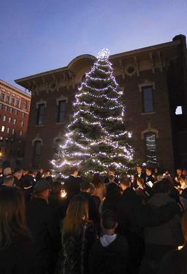 Katie Fyfe | The Journal Gazette Families honor departed loved ones Sunday evening during  Visiting Nurse's 34th annual Holiday Memorial Service and Tree Lighting outside the  University of Saint Francis' Robert Goldstine Performing Arts Center downtown.