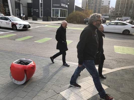 Piaggio Fast Forward CEO Greg Lynn, center, is followed by his company's Gita carrier robot as he crosses a street on Monday, Nov. 11, in Boston. (AP Photo / Matt O'Brien)