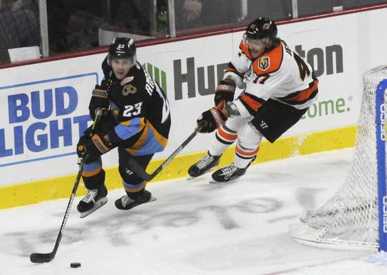 Justin A. Cohn | The Journal Gazette  Komets forward A.J. Jenks, right, chases the Toledo Walleye's Brandon Anselmini for the puck at the Huntington Center in Toledo, Ohio.