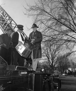 File March 31, 1957: Assistant Fire Chief Maine Graft, center, and firefighter Walter Roemke check over a duck before it is placed in a box to for transport to a bird sanctuary.