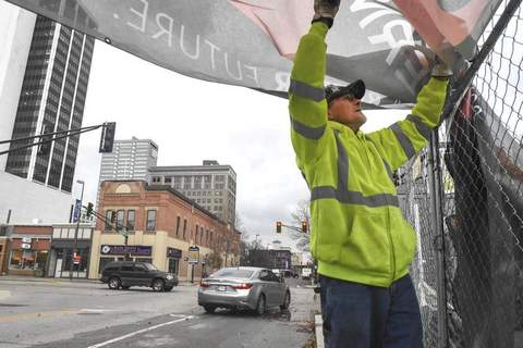 Scott McMullen with Hagerman Construction takes down the fence screen along Harrison Street on Wednesday after high wind hit the city. (Michelle Davies | The Journal Gazette)