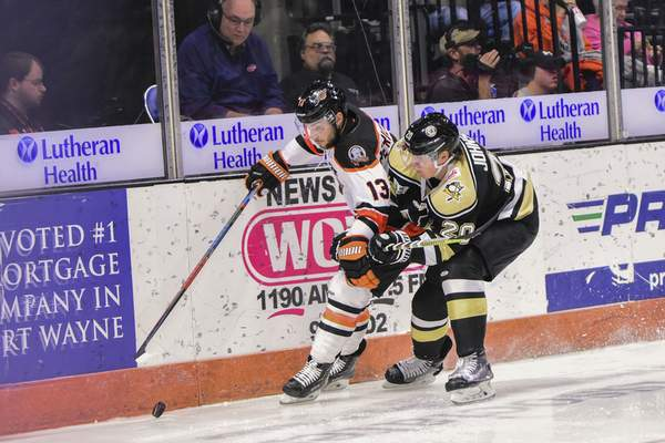 Mike Moore   The Journal Gazette Komets forward Anthony Petruzzelli and Nailers defenseman Steve Johnson race for the puck in the first period at Memorial Coliseum on Thursday.