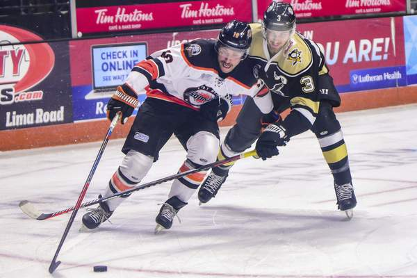 Mike Moore | The Journal Gazette Komets forward Brady Shaw and Nailers defenseman Aaron Titcomb fight for the puck in the first period at Memorial Coliseum on Thursday.
