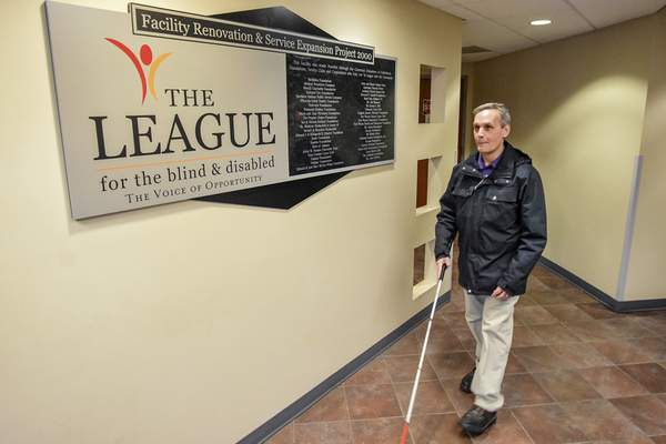 Fred Fulkerson, senior blind services coordinator, walks in the hallway at The League for the Blind and Disabled whichprovides services and promotes opportunities that empower people with disabilities to achieve their potential. (Photos by Mike Moore | The Journal Gazette)