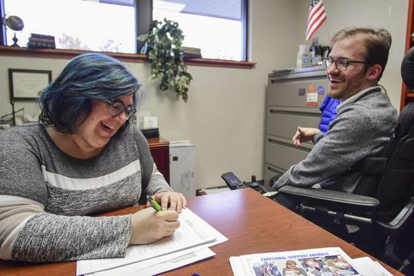 Laura Lindsay, director of programming and services, fills out a housing application with Luke Labas at The League for the Blind and Disabled.