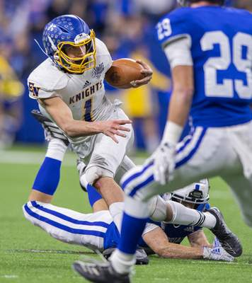 East Noble High School senior Bailey Parker (1) is tripped up by Evansville Memorial High School sophomore Connor Agler (4) during the first half of action in the 47th annual IHSAA class 4A football state finals at Lucas Oil Stadium, Saturday, Nov. 30, 2019. Evansville Memorial High School won 21-3. (Doug McSchooler/for Journal-Gazette)