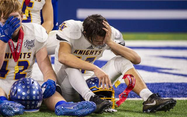Photos by Doug McSchooler | For Journal-Gazette Emotional East Noble players Gage Ernsberger, right, and Caden Conley sit on the field at Lucas Oil Stadium on Saturday.