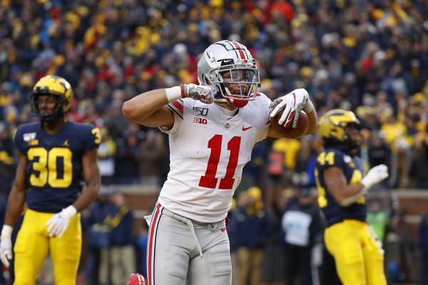 Associated Press Ohio State wide receiver Austin Mack, a Bishop Luers graduate, celebrates after scoring on a 16-yard touchdown reception against the Wolverines in Ann Arbor, Mich., on Saturday.