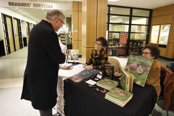 Photos by Rachel Von Stroup | The Journal Gazette Harry J. Reith talks with local author Kylee Baumle and her mother, Louise Hartwig, during Saturday's Local Author Book Sale at the downtown Allen County Public Library.