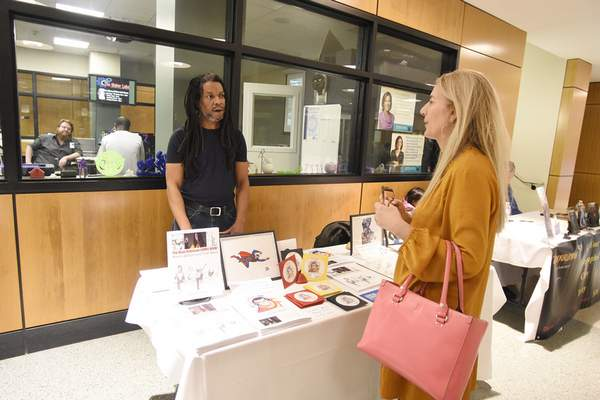 Local authors Dean Robinson and Anmarie Uber chat during Saturday's book sale at the Allen County Public Library.