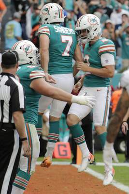 Miami Dolphins kicker Jason Sanders (7) and punter Matt Haack (2) celebrate after Sanders scored a touchdown thrown by Haack, during the first half at an NFL football game against the Philadelphia Eagles, Sunday, Dec. 1, 2019, in Miami Gardens, Fla. (AP Photo/Lynne Sladky)