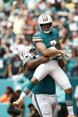 Miami Dolphins defensive tackle Christian Wilkins (94) lifts kicker Jason Sanders (7), after Sanders caught a touchdown pass, during the first half at an NFL football game against the Philadelphia Eagles, Sunday, Dec. 1, 2019, in Miami Gardens, Fla. (AP Photo/Brynn Anderson)