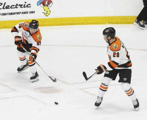 Justin A. Cohn | The Journal Gazette  Komets forward AlanLyszczarczyk, left, passes the puck up ice as teammate Matthew Boudens looks on at Wings Event Center on Sunday.