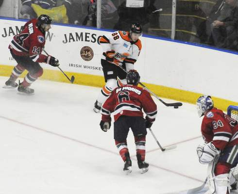 Justin A. Cohn | The Journal Gazette  Komets forward AlanLyszczarczyk, top, looks to pass the puck Sunday with the Kalamazoo Wings' Matt VanVoorhis in his face at Wings Event Center. Ben Wilson, left, and goalie Jake Kielly, right, look on.