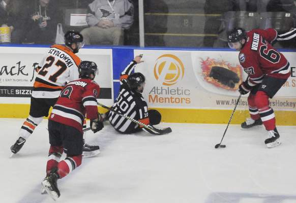 Justin A. Cohn | The Journal Gazette  Referee Brett Roeland, middle, recovers from a spill as the Kalamazoo Wings' Yannick Vailleux and the Komets' Shawn Szydlowski battle for posession of the puck at Wings Event Center.