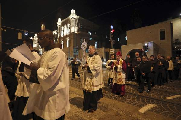 Christian clergymen carry a wooden relic believed to be from Jesus' manger outside the Notre Dame church in Jerusalem, Friday, Nov. 29, 2019. (AP Photo/Mahmoud Illean)