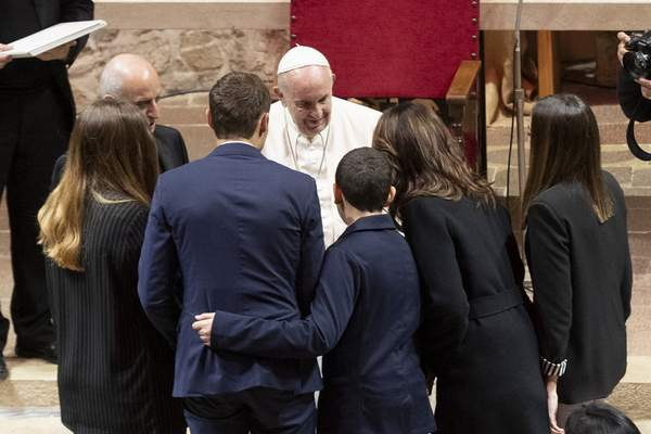 Associated Press Pope Francis meets a family in the sanctuary of Greccio, Italy, on Sunday. Francis urged Nativity creches be placed in public places.