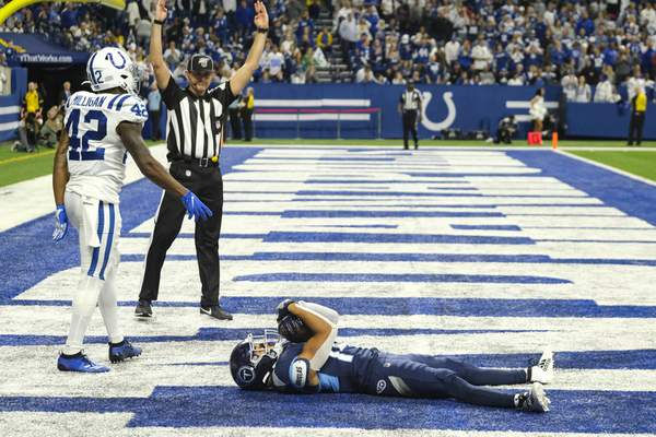 Associated Press photos Titans wide receiver Kalif Raymond lies in the end zone after scoring a fourth-quarter touchdown in front of Colts defensive back Rolan Milligan on Sunday. Raymond's TD sealed Tennessee's come-from-behind win.