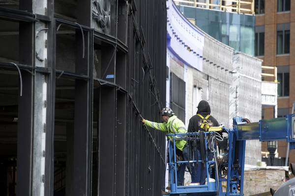 In this Wednesday, Nov. 27, 2019 photo workers use a lift while working on a new building in Boston's Seaport district.  (AP Photo/Steven Senne)