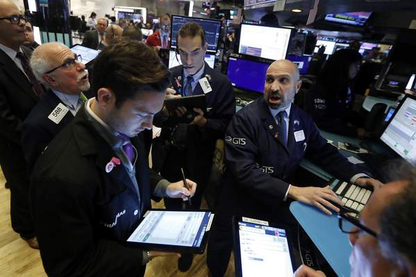 FILE - In this Nov. 14, 2019, file photo specialist James Denaro, right, works with traders at his post on the floor of the New York Stock Exchange. (AP Photo/Richard Drew, File)