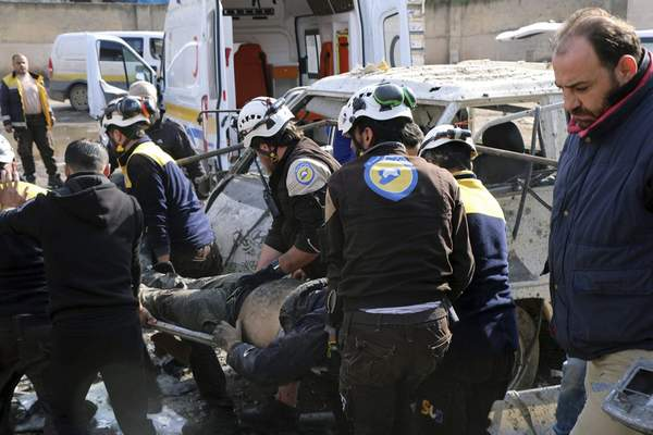 This photo provided by the Syrian Civil Defense White Helmets, which has been authenticated based on its contents and other AP reporting, shows members of the Syrian Civil Defense transporting an injured person after an airstrike hit the northern town of Maaret al-Numan, in Idlib province, Syria, Monday, Dec. 2, 2019. (Syrian Civil Defense White Helmets via AP)