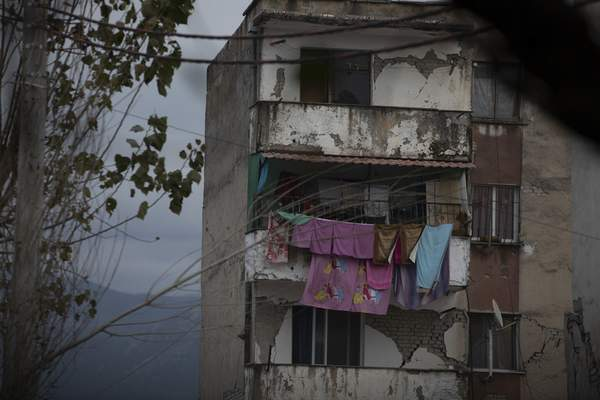 In this Wednesday, Nov. 27, 2019 photo, laundry hangs on a line from a damaged building in Thumane, western Albania following a deadly earthquake. (AP Photo/Petros Giannakouris)