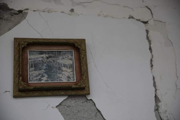 In this Thursday, Nov. 28, 2019 photo a frame which has turned up side down on a wall of a damaged building in Durres, western Albania following a deadly earthquake.(AP Photo/Petros Giannakouris)
