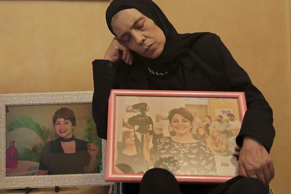 In this Nov. 17, 2019 photo, Majida holds a photo of her daughter Nadyn Jouny as she attends a 40 day mourning ceremony of her death in a car accident, at their family house in southern Beirut, Lebanon. (AP Photo/Hassan Ammar)