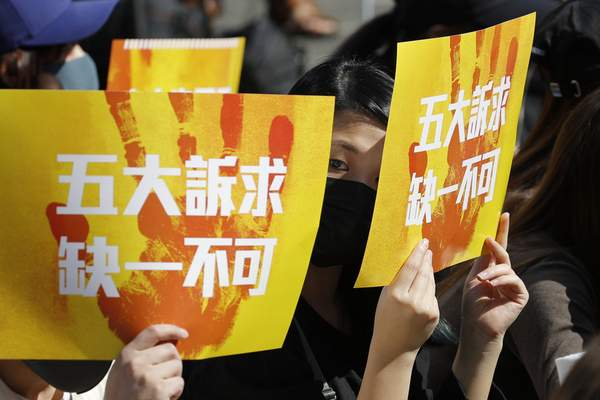 Pro-democracy supporters hold up cards which read Five Demands, Not one less during a rally by the advertising industry in Hong Kong Monday, Dec. 2, 2019. (AP Photo/Vincent Thian)
