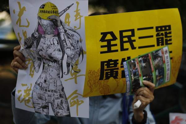 An anti-government supporter holds up banners during a rally by the advertising industry in Hong Kong on Monday, Dec. 2, 2019. (AP Photo/Vincent Thian)